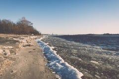 Frozen beach near shipyard and sea port - vintage retro effect Royalty Free Stock Photo