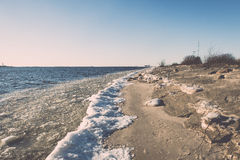 Frozen beach near shipyard and sea port - vintage retro effect Royalty Free Stock Photo