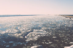 Frozen beach near shipyard and sea port - vintage retro effect Royalty Free Stock Photography