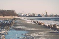 Frozen beach near shipyard and sea port - vintage retro effect Stock Photo
