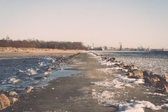 Frozen beach near shipyard and sea port - vintage retro effect Royalty Free Stock Images