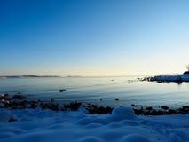 Frozen beach. At sunset on the coast of Norway stock photo