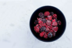 Frozen Berries in black bowl on white marble surface Stock Image