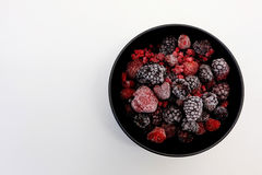 Frozen Berries in black bowl on white surface Stock Images