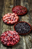 Frozen berries in bowls on wooden background. Selective focus. Stock Photos
