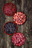 Frozen berries in four bowls on wooden background. Top view. Frozen berries in four bowls on the wooden background. Top view Stock Photos