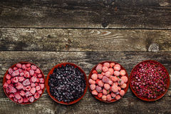 Frozen berries in four bowls on wooden background. Top view. Space for text. Frozen berries in four bowls on the wooden background. Top view. Space for text Royalty Free Stock Photography