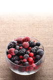 Frozen berries in glass bowl  burlap canvas Stock Image