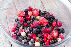 Frozen berries in a glass bowl, closeup. Frozen berries in a glass bowl, on a wooden background Stock Photography