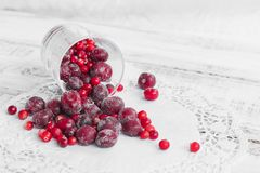 Frozen berries in a glass cup on the light wooden background. Cherry and cranberry stock image