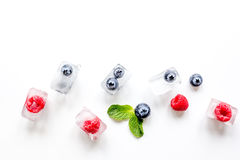 Frozen berries in ice cubes with mint on white background mock-up. Frozen bueberrie and raspberrie in ice cubes with mint on white table background mock-up Royalty Free Stock Photography