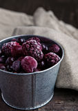 Frozen berries mix in a black bowl on wooden background. Still life photography Royalty Free Stock Image