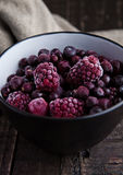 Frozen berries mix in a black bowl on wooden background. Still life photography Royalty Free Stock Images