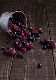 Frozen berries mix in a black bowl on wooden background. Still life photography Royalty Free Stock Photo