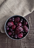 Frozen berries mix in small steel bucket on wooden table. With kitchen towel Stock Photo