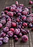 Frozen berries mix in small steel bucket on wooden table. With kitchen towel Stock Photography