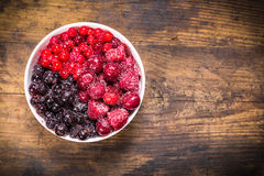 Frozen berries in plate on wooden background Stock Photos