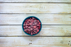 Frozen berries raspberries village. Frozen raspberries in a clay bowl on a wooden table. Beautiful berries background. Macro image royalty free stock photography