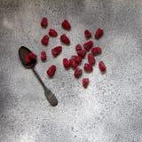 Frozen berries of raspberries on vintage spoon on concrete backg. Frozen berries of raspberries on a vintage silver spoon on a gray concrete background. Top view Royalty Free Stock Image