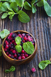 Frozen berries, red and black currants, blueberries and raspberr. Ies with fresh mint leaves in wooden bowl Royalty Free Stock Photography