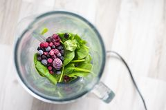 Frozen berries and spinach leaf ready for smoothie blending.  stock photography