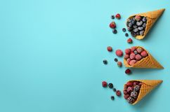 Frozen berries - strawberry, blueberry, blackberry, raspberry in waffle cones on blue background. Top view. Banner Royalty Free Stock Photos