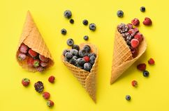 Frozen berries - strawberry, blueberry, blackberry, raspberry in waffle cones on yellow background. Top view. Banner Stock Image