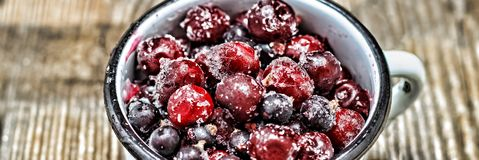 Closeup. Frozen berries in a white cup on a wooden table. Frozen berries in a white cup on a wooden table. Closeup Stock Image