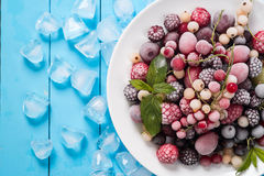 Frozen berry on turquoise background top view Royalty Free Stock Photo