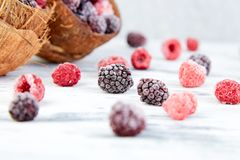 Frozen black and red raspberries in coconut bowl. Frozen black and red raspberries in coconut bowl Stock Photos