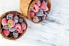 Frozen black and red raspberries in coconut bowl. Top view Stock Images
