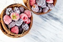 Frozen black and red raspberries in coconut bowl. Top view Stock Image