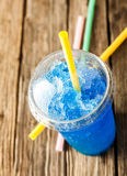 Frozen Blue Slushie in Plastic Cup with Straw. High Angle View of Refreshing and Cool Frozen Blue Fruit Slush Drink in Plastic Cup with Lid Served on Rustic royalty free stock photography