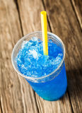 Frozen Blue Slushie in Plastic Cup with Straw. High Angle View of Refreshing and Cool Frozen Blue Fruit Slush Drink in Plastic Cup Served on Rustic Wooden Table stock photos