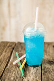 Frozen Blue Slushie in Plastic Cup with Straw. Still Life Profile View of Refreshing and Cool Frozen Turquoise Fruit Slush Drink in Plastic Cup with Lid Served stock image