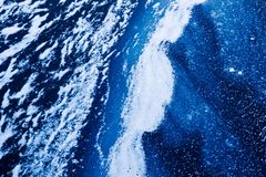 Frozen blue water surface and wave covered with ice, snow abstract winter background wallpaper stock photography
