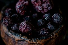 Frozen blueberries in a clay bowl with dark background close up. Frozen blueberries in  a clay bowl with dark background close up Royalty Free Stock Photo