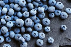 Frozen blueberry on black slate. Close up. Top view. High resolution product. Healthy food Stock Image