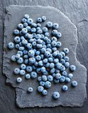 Frozen blueberry on black slate. Top view. High resolution product. Healthy food Stock Photo