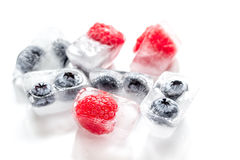 Frozen blueberry and raspberry in icecubes on white background Stock Photo