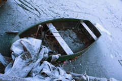 Frozen boat. On a frozen lake with debris royalty free stock images