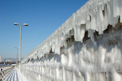 Frozen breakwater with icicles against blue sky Royalty Free Stock Photography