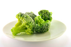 Frozen Broccoli. Four pieces of frozen broccoli on a white plate with a plain background Royalty Free Stock Photo