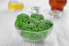 Frozen broccoli in bowl. On wooden background Royalty Free Stock Photography