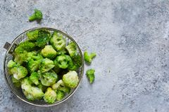 Frozen broccoli on a concrete background with space for text, healthy diet food. view from above. Frozen broccoli on a concrete background with space for text royalty free stock images