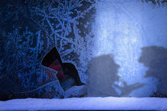 Frozen broken window with a hole and two  silhouettes Royalty Free Stock Image