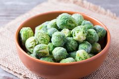 Frozen Brussels sprouts in a bowl on a wooden table. Frozen Brussels sprouts in a bowl on a table Royalty Free Stock Photography