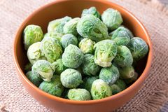 Frozen Brussels sprouts in a bowl on a wooden table. Frozen Brussels sprouts in a bowl on a table Stock Images