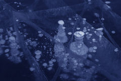 Frozen bubbles and cracks in the transparent ice. Royalty Free Stock Photography