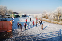 Frozen Canals in Holland. Dutch Winter Landscape. Ice skaters in a Dutch Winter in a landscape with windmills Royalty Free Stock Photo